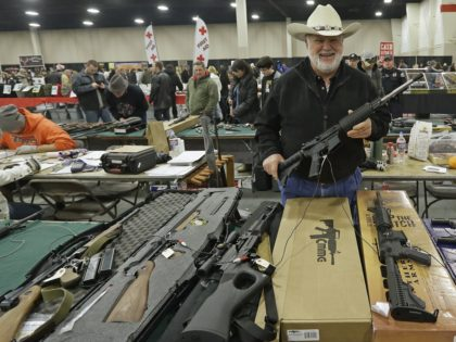 """FILE - In this Jan. 6, 2013 file photo, Ken Haiterman, of Pioneer Market, holds a CMMG 5.56mm AR 15 during the 2013 Rocky Mountain Gun Show in Sandy, Utah. A bipartisan quartet of senators, including two National Rifle Association members and two with """"F"""" ratings from the potent firearms …"""
