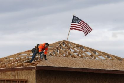 The American flag flutters in the wind as work is done on the roof of a building under construction in Sacramento, Calif., Tuesday, March 31, 2020. While most Californian's have spent more than a week under a mandatory stay-at-home order, because of the coronavirus, construction work is among the jobs …