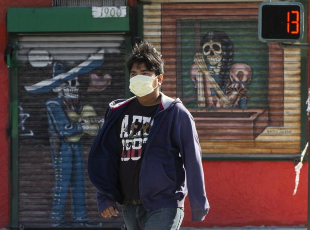 A pedestrian wears a face mask in the Boyle Heights area of Los Angeles on Wednesday, April 1, 2020. Los Angeles Mayor Eric Garcetti has recommended that the city's 4 million people wear masks when going outside amid the spreading coronavirus. Garcetti on Wednesday said people in the nation's second-largest …