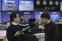 A currency trader checks the temperature of his colleague at the foreign exchange dealing room of the KEB Hana Bank headquarters in Seoul, South Korea, Friday, April 3, 2020. Asian stocks were mixed Friday after Wall Street gained for the first time in three days on stronger oil prices despite …