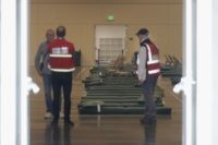 A group of officials stand in front of beds at Moscone West in San Francisco, Thursday, April 2, 2020. Since the beginning of the international pandemic, officials in California have said one population is particularly vulnerable to contracting the coronavirus and spreading it to others: the homeless. Officials are setting …