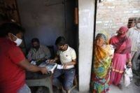 An Impoverished Indians gives his finger print on a biometric machine after purchasing food ration in Prayagraj, India, Thursday, April 2, 2020. India is adding more resources to tackle its increase in coronavirus cases by announcing that private hospitals may be requisitioned to help treat virus patients, and turning railway …