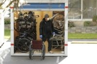 A worker at the Life Care Center in Kirkland, Wash., looks through a storage container filled with wheelchairs, walkers, and other mobility devices, Thursday, April 2, 2020. Federal authorities on Wednesday, April 1, 2020, proposed a fine of more than $600,000 for the Seattle-area nursing home connected to at least …