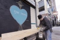 A carpenter, who declined to be identified, cuts plywood to cover a closed store where artwork in support of people affected by the coronavirus already covers an adjacent panel in downtown Seattle, Thursday, April 2, 2020. The number of people seeking unemployment benefits in Washington set a new record last …