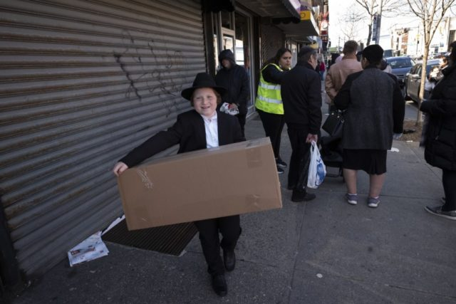 In this Thursday, March 26, 2020 file photo, a boy carries a box of matzos for Passover that he picked up from his synagogue in the Brooklyn borough of New York. The coronavirus has forced Jewish families to limit the celebratory Passover meals known as seders from extended families and …