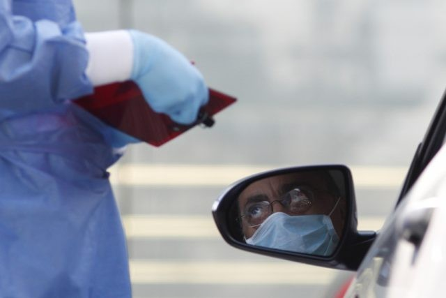 A doctor gathers information from a driver arriving to get tested for COVID-19 at private laboratory Biomedica de Referencia, in the Lomas Virreyes neighborhood of Mexico City, Thursday, March 26, 2020. The new coronavirus causes mild or moderate symptoms for most people, but for some, especially older adults and people …