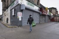In this Friday, April 3, 2020, photo, a woman walks by local stores during the coronavirus pandemic in New York. Small business owners hoping for quick help from the government's emergency $349 billion lending program were still waiting Tuesday, April 7, 2020, amid reports of computer problems at the Small …