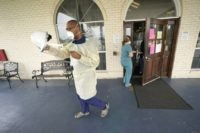 Dr. Robin Armstrong puts on his face shield while demonstrating his full personal protective equipment outside the entrance to The Resort at Texas City nursing home, where he is the medical director, Tuesday, April 7, 2020, in Texas City, Texas. Armstrong is treating nearly 30 residents of the nursing home …