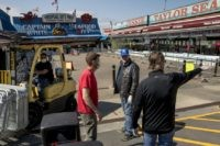 In this April 6, 2020, photo, Billy White, right, and his brother Sonny White, second from right, owners of Captain White Seafood City, along with their nephew Paul White, left, and Stan Kiser with Jessie Taylor Seafood, second from left, set up portable fencing in the hope to force customers …