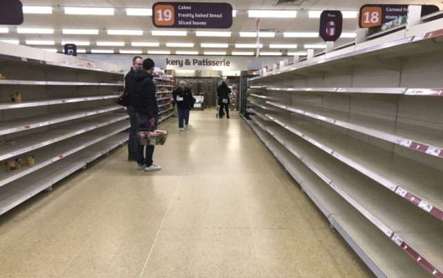 In this Thursday, March 19, 2020 file photo, people stand in an aisle of empty shelves in a supermarket in London, amid panic-buying due to the coronavirus outbreak. A pandemic forcing everyone to stay home could be the perfect moment for online grocery services. In practice, they've been struggling to …