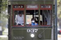In this March 19, 2020 file photo, a streetcar conductor wears a mask due to the coronavirus pandemic as she runs her route on St. Charles Ave. in New Orleans. Where political divides marred early recovery efforts after Hurricane Katrina in 2005, Louisiana is showing rare political unity in the …