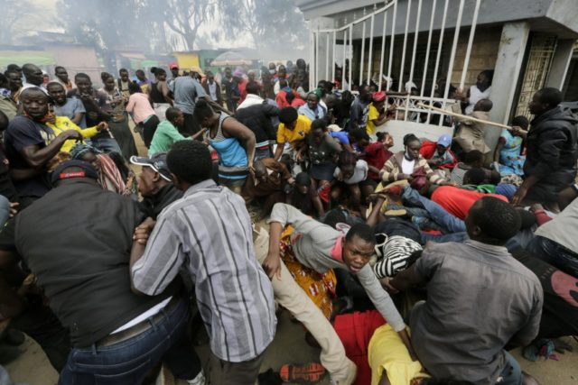 Residents desperate for a planned distribution of food for those suffering under Kenya's coronavirus-related movement restrictions push through a gate and create a stampede, causing police to fire tear gas and leaving several injured, at a district office in the Kibera slum, or informal settlement, of Nairobi, Friday, April 10, …