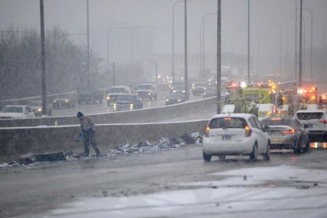An Illinois State Trooper piles up debris on the side of the Kennedy Expressway after a 54 car pile-up early morning Wednesday, April 15, 2020, in Chicago. The Chicago Fire Department says about 50 vehicles were involved in the pileup along the expressway. (AP Photo/Paul Beaty)