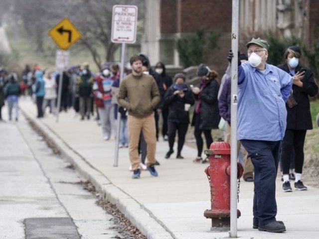 In this April 7, 2020, photo, voters masked against coronavirus line up at Riverside High School for Wisconsin's primary election in Milwaukee. The devastating coronavirus pandemic stands poised to reshape the political map this November. The virus has pummeled battleground states and alarmed Republicans who see early warning signs for …