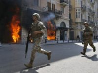 Lebanese army soldiers run in front of a Credit Libanais Bank that was set on fire by anti-government protesters, in the northern city of Tripoli, Lebanon, Tuesday, April 28, 2020. Hundreds of angry Lebanese took part Tuesday in the funeral of a young man killed in riots overnight in the …