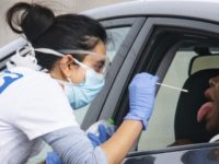 A medical worker takes a swab at a drive-in coronavirus testing facility at the Chessington World of Adventures Resort in Chessington, England, Wednesday April 29, 2020. Coronavirus testing is now available for more people in England from Wednesday as the government relaxed rules on eligibility. (Aaron Chown/PA via AP)