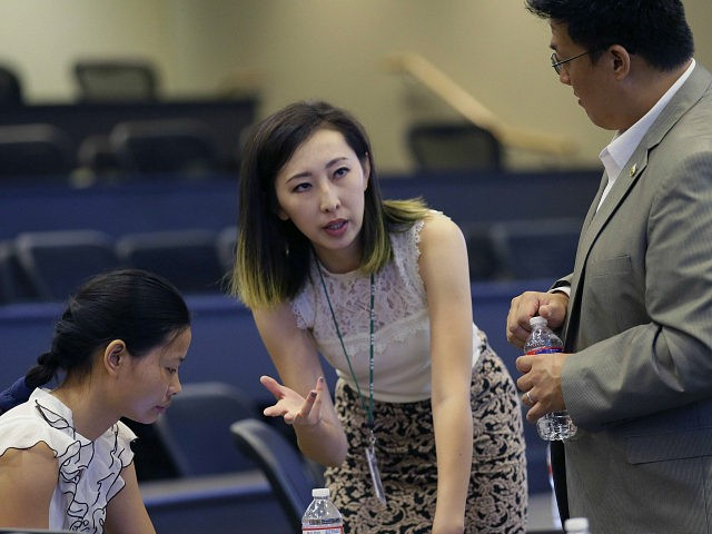 In this photo made Saturday, Aug. 22, 2015, Hua Bai, center, vice president of Friendship Association of Chinese Scholars and Students, prepares for an orientation for fellow Chinese students at the University of Texas at Dallas in Richardson, Texas. Bai from China last year to work on a master's degree …