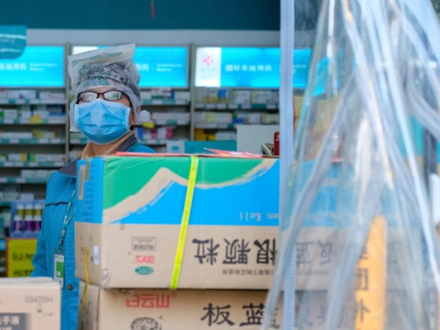A clerk wearing a face mask and a plastic bag stands in a pharmacy in Wuhan in central China's Hubei Province, Friday, Jan. 31, 2020. The U.S. advised against all travel to China as the number of cases of a worrying new virus spiked more than tenfold in a week, …