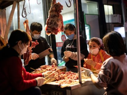 Workers wearing facemasks make a barbecue at a market in Wuhan, in China's central Hubei province on April 4, 2020. - China came to a standstill on Saturday to mourn patients and medical staff killed by the coronavirus, as the world's most populous country observed a nationwide three-minute silence. (Photo …