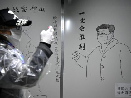 A man walks in front of a drawing of Chinese President Xi Jinping on a wall at the Leishenshan Hospital that had offered beds for coronavirus patients in Wuhan, in Chinas central Hubei province on April 11, 2020. (Photo by Noel Celis / AFP) (Photo by NOEL CELIS/AFP via Getty …