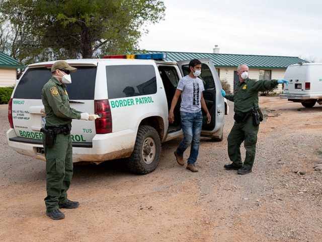 Border Patrol agents utilizing PPE and coronavirus protection protocols while processing an illegal alien. (CBP File Photo by Jerry Glaser)