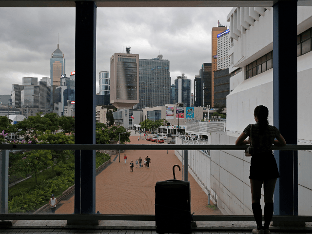 """In this June 10, 2019, photo, a woman stands near the skyline of Hong Kong at Central, business district of Hong Kong. It's still the world's """"freest"""" economy, one of the biggest global financial centers and a scenic haven for tycoons and tourists, but the waves of protests rocking Hong …"""