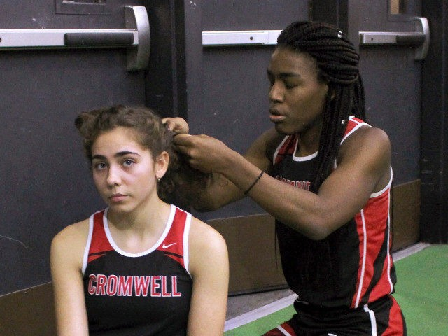 FILE - In this Feb. 7, 2019 file photo, Cromwell High School transgender athlete Andraya Yearwood, right, braids the hair of teammate Taylor Santos during a break at a track meet at Hillhouse High School in New Haven, Conn. The federal Office for Civil Rights has launched an investigation into …