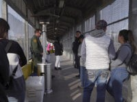 A Border Patrol agent, back left, and a U.S. Customs and Border Protection agent, right, oversee the port of entry at the Gateway International Bridge, while people wait in line to cross into the U.S. from Matamoros, Mexico, at the Port of Entry in Brownsville, Texas, Tuesday, Dec. 17, 2019. …