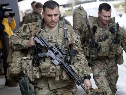 U.S. Army soldiers with their gear head to an awaiting bus Saturday, Jan. 4, 2020 at Fort Bragg, N.C., as troops from the 82nd Airborne are deployed to the Middle East as reinforcements in the volatile aftermath of the killing of Iranian Gen. Qassem Soleimani. (AP Photo/Chris Seward)