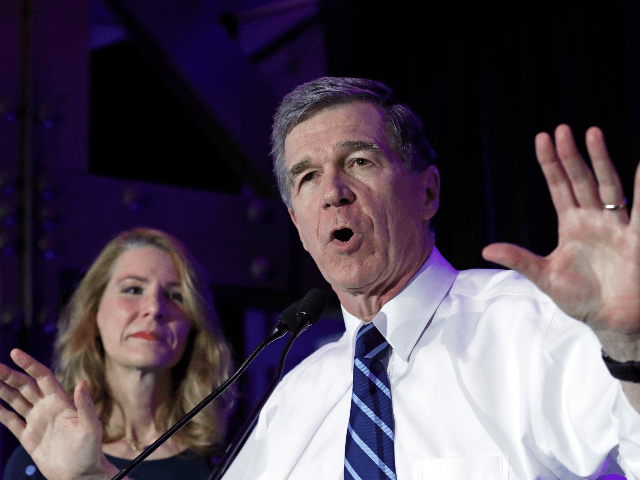 North Carolina Gov. Roy Cooper speaks to supporters while joined by his wife Kristin during a primary election night party in Raleigh, N.C., Tuesday, March 3, 2020. (AP Photo/Gerry Broome)