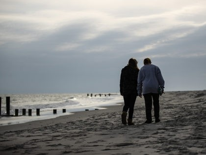 People walk on the beach in Cape May, N.J., Wednesday, March 18, 2020. Some people who live in cities or their suburbs have been fleeing to their second homes at the shore to ride out the coronavirus near the beach. But neighbors in many of those towns are yanking the …