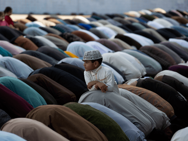 A Pakistani boy stands amid of people offer Friday prayers besides government's advice to avoid public gathering to avoid contracting coronavirus, at a local mosque in Rawalpindi, Pakistan, Pakistan, March 20, 2020. The vast majority of people recover from the new coronavirus. According to the World Health Organization, most people …