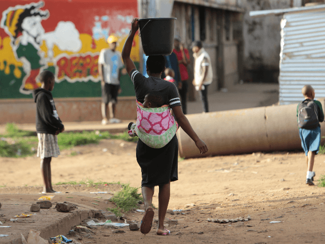 In this Monday, April 6, 2020 photo, a woman carries a her baby and a bucket of water in Harare. Lockdowns imposed to curb the coronavirus' spread have put millions of women in Africa, Asia and elsewhere out of reach of birth control and other sexual and reproductive health needs. …