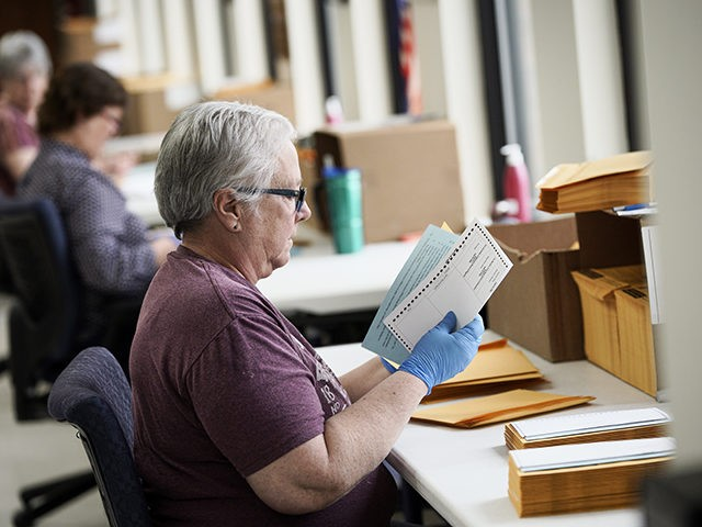 In this April 14, 2020 photo, Pam Fleming and fellow workers stuff ballots and instructions into mail-in envelopes at the Lancaster County Election Committee offices in Lincoln, Neb. Officials in Nebraska are forging ahead with plans for the state's May 12 primary despite calls from Democrats to only offer voting …