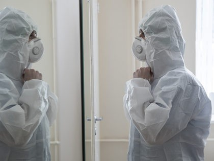 In this photo taken on Tuesday, April 21, 2020, a medical worker puts on protective gear in order to assist coronavirus patients at the intensive care unit of Vinogradov City Clinical Hospital in Moscow, Russia. Reports of Russian medical workers becoming infected with the coronavirus are emerging almost daily as …