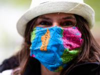 A woman wears a wears a face mask with a world map design as the attends a protest of travel agents in Kiel, Germany, Wednesday, Aril 29, 2020. Representatives of tour operators and travel agencies demonstrated in front of the Kiel state parliament to draw attention to their difficult economic …