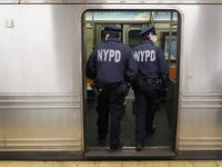 NYPD officers wake up sleeping passengers and direct them to the exits at the 207th Street A-train station, Thursday, April 30, 2020, during the coronavirus pandemic, in the Manhattan borough of New York. (AP Photo/John Minchillo)