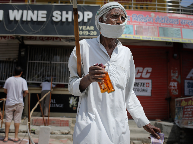 An elderly Indian man walks with two bottles of liquor purchased from one of the liquor shops which was reopened Monday after six weeks lockdown on the outskirts of New Delhi, India, Monday, May 4, 2020. India's six-week coronavirus lockdown, which was supposed to end on Monday, has been extended …