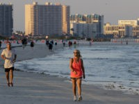 People run and walk along Clearwater Beach after it was reopened to the public Monday, May 4, 2020, in Clearwater Beach, Fla. Many public beaches and restaurants are reopening as part of Florida Gov. Ron DeSantis' phase one to stop the spread of the coronavirus. (AP Photo/Chris O'Meara)