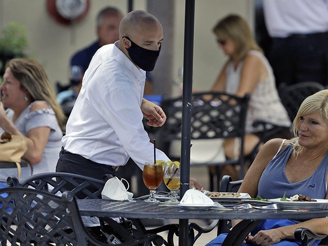 A foodserver at the Parkshore Grill restaurant wears a protective face mask as he waits on customers Monday, May 4, 2020, in St. Petersburg, Fla. Several restaurants are reopening with a 25% capacity as part of Florida Gov. Ron DeSantis' plan to stop the spread of the coronavirus. (AP Photo/Chris …