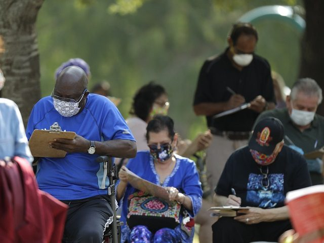 People wait in line at a free walk-up COVID-19 test site, Friday, May 8, 2020, in San Antonio. Texas' stay-at-home orders due to the COVID-19 pandemic have expired and Texas Gov. Greg Abbott has eased restrictions on many businesses, churches, state parks and beaches. (AP Photo/Eric Gay)