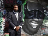 Lee Merritt, a lawyer representing the family of Ahmaud Arbery, poses for a photo by a mural in the likeness of Arbery painted by artist Theo Ponchaveli in Dallas, Saturday, May 9, 2020. Arbery's mother, Wanda Cooper Jones, has said she thinks her son, a former high school football player, …