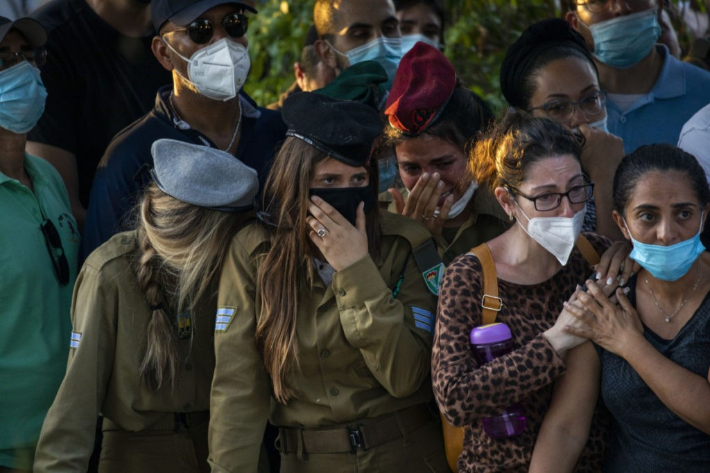 Israeli soldiers and civilians wear face masks to protect against the spread of the coronavirus during the funeral of Israeli army Staff Sgt. Amit Ben-Yigal in Beer Yaakov, Israel, Tuesday, May 12, 2020. Ben Ygal, 21, was killed early Tuesday during a West Bank arrest raid when a rock thrown off a rooftop struck him in the head, the military said, capping a surge in violence ahead of a visit to the region by the U.S. Secretary of State. (AP Photo/Ariel Schalit)