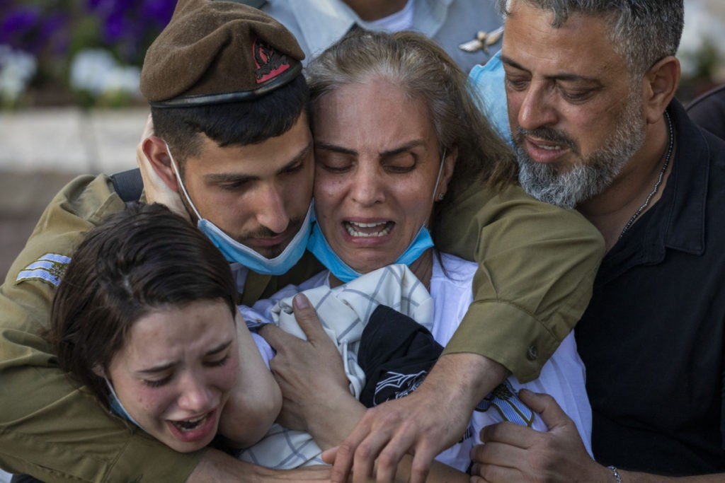 Nava, mother of Israeli army Staff Sgt. Amit Ben-Yigal, grieves during his funeral as soldiers and family wear face masks to protect against the spread of the coronavirus in Beer Yaakov, Israel, Tuesday, May 12, 2020. Ben Ygal, 21, was killed early Tuesday during a West Bank arrest raid when a rock thrown off a rooftop struck him in the head, the military said, capping a surge in violence ahead of a visit to the region by the U.S. secretary of state. (AP Photo/Ariel Schalit)