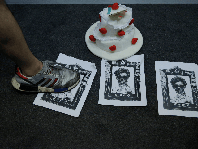 A protester steps on the placards featuring a sketch of Hong Kong Chief Executive Carrie Lam and a mock birthday cake during an anti-government protest in Hong Kong, Wednesday, May, 13, 2020. A pro-democracy movement that paralyzed Hong Kong for months last year has shown signs of reviving in recent …