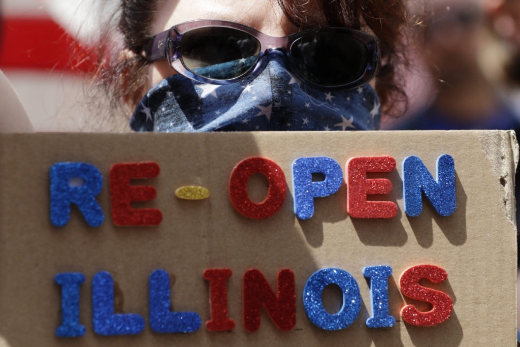 A protester holds a sign during a rally calling for the state to reopen the economy, Saturday, May 16, 2020, outside the Thompson Center in downtown Chicago. (AP Photo/Nam Y. Huh)