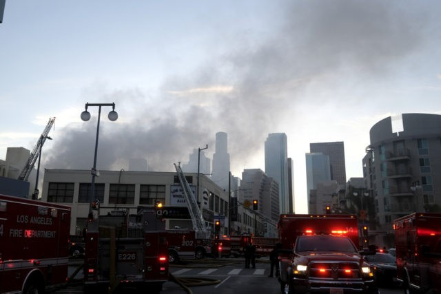 Smoke rises from the scene of a structure fire that injured multiple firefighters, according to a fire department spokesman, Saturday, May 16, 2020, in Los Angeles. (AP Photo/Ringo H.W. Chiu)