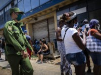 People wearing masks as a precaution against the spread of the new coronavirus talk to each other while waiting in front of a store to buy food in Havana, Cuba, Tuesday, May 19, 2020. Cuban authorities are requiring the use of masks for anyone outside their homes . (AP Photo …