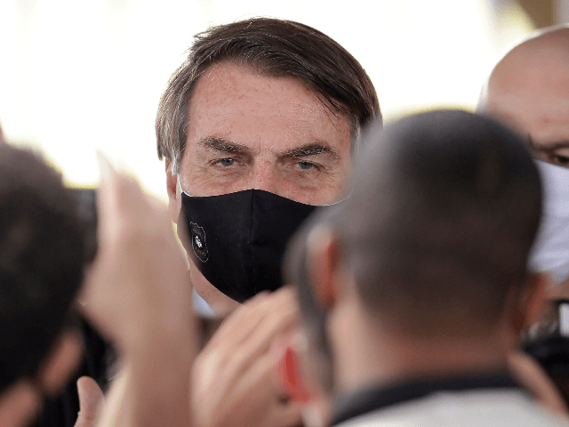 Brazil's President Jair Bolsonaro, wearing a face mask amid the new coronavirus, faces supporters as he departs his official residence of Alvorada palace in Brasilia, Brazil, Monday, May 25, 2020. (AP Photo/Eraldo Peres)