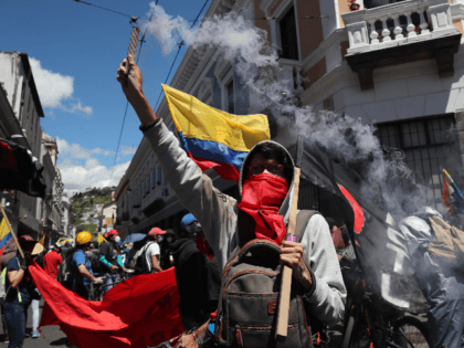 A protester holds a flare during a workers' unions protest against government reforms to fight the economic and health crisis brought by the COVID-19 pandemic in Quito, Ecuador, Monday, May 25, 2020. Worker unions say the reforms include shortening workdays from 8 to 6 hours, thus lowering pay, and criticize …